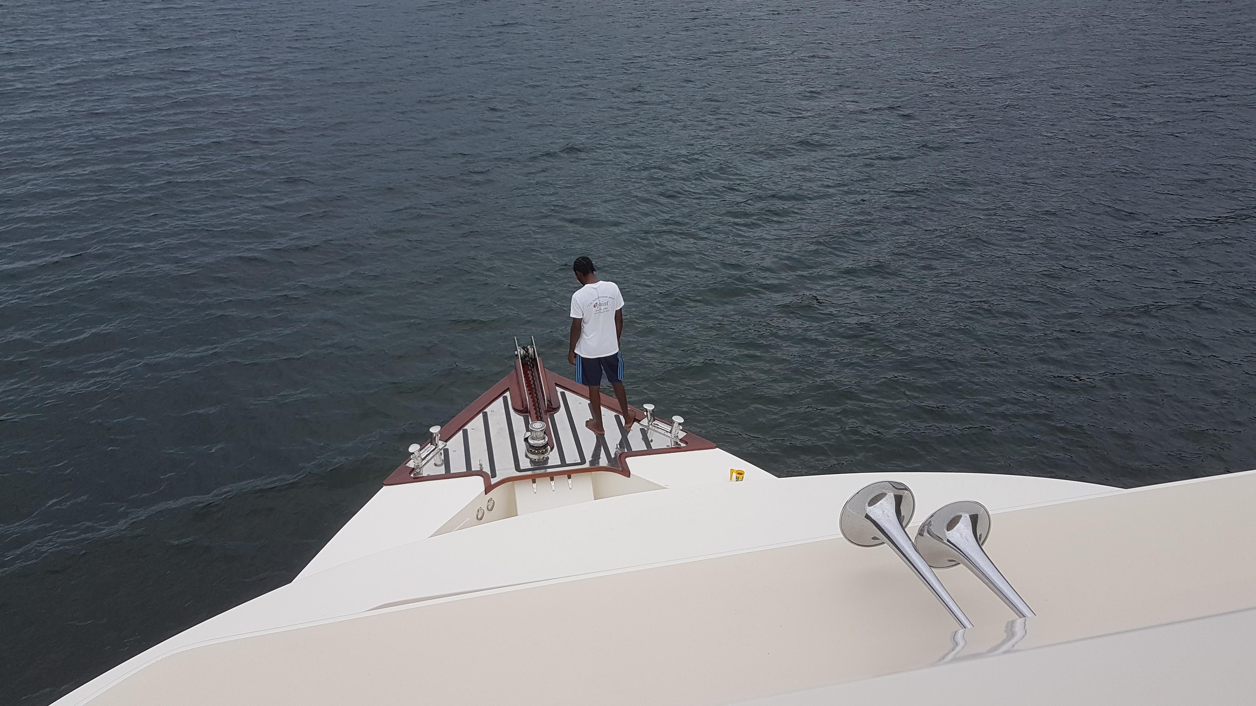 Crew at bow raising anchor