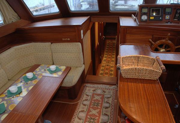 Salon With Helm Inside. Open Galley And Dining Table